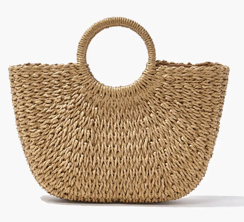 A straw tote bag with a big circular handle resting on the ground
