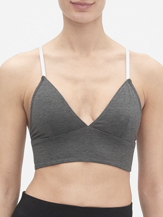 a woman wearing a grey bralette with white straps