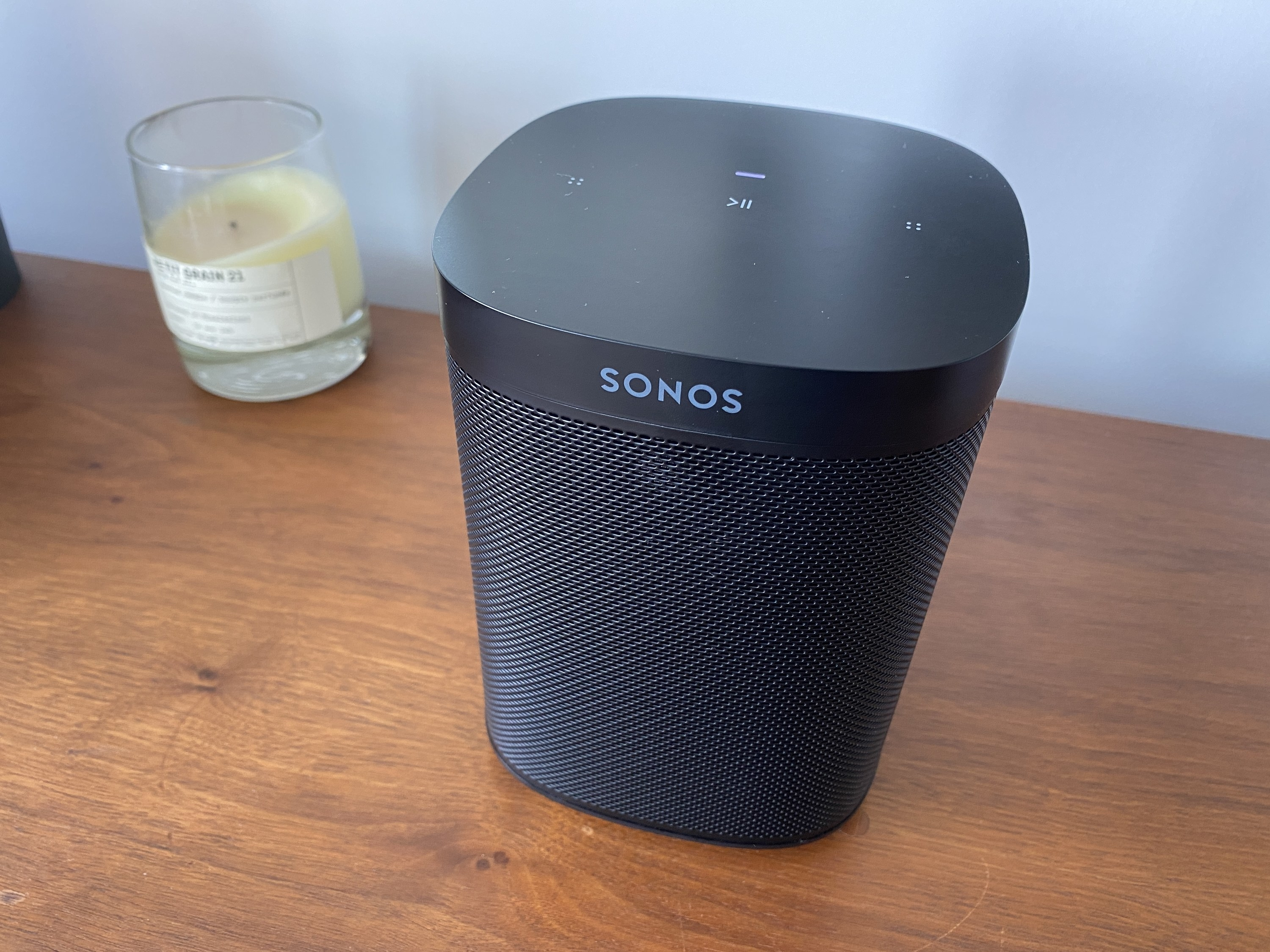 A black Sonos One SL wireless speaker on a wooden table