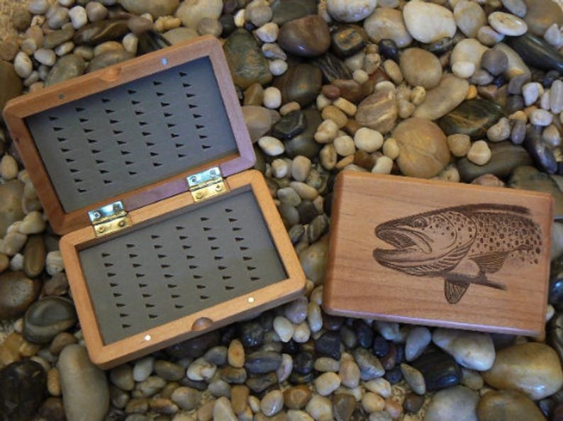 open fly fishing case on a bed of rocks