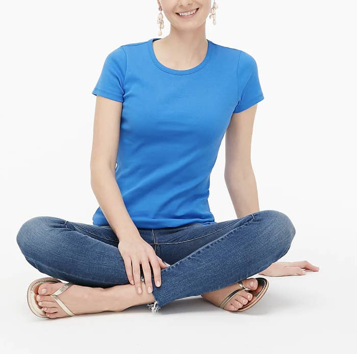 A model wears the tee in a sea blue shade