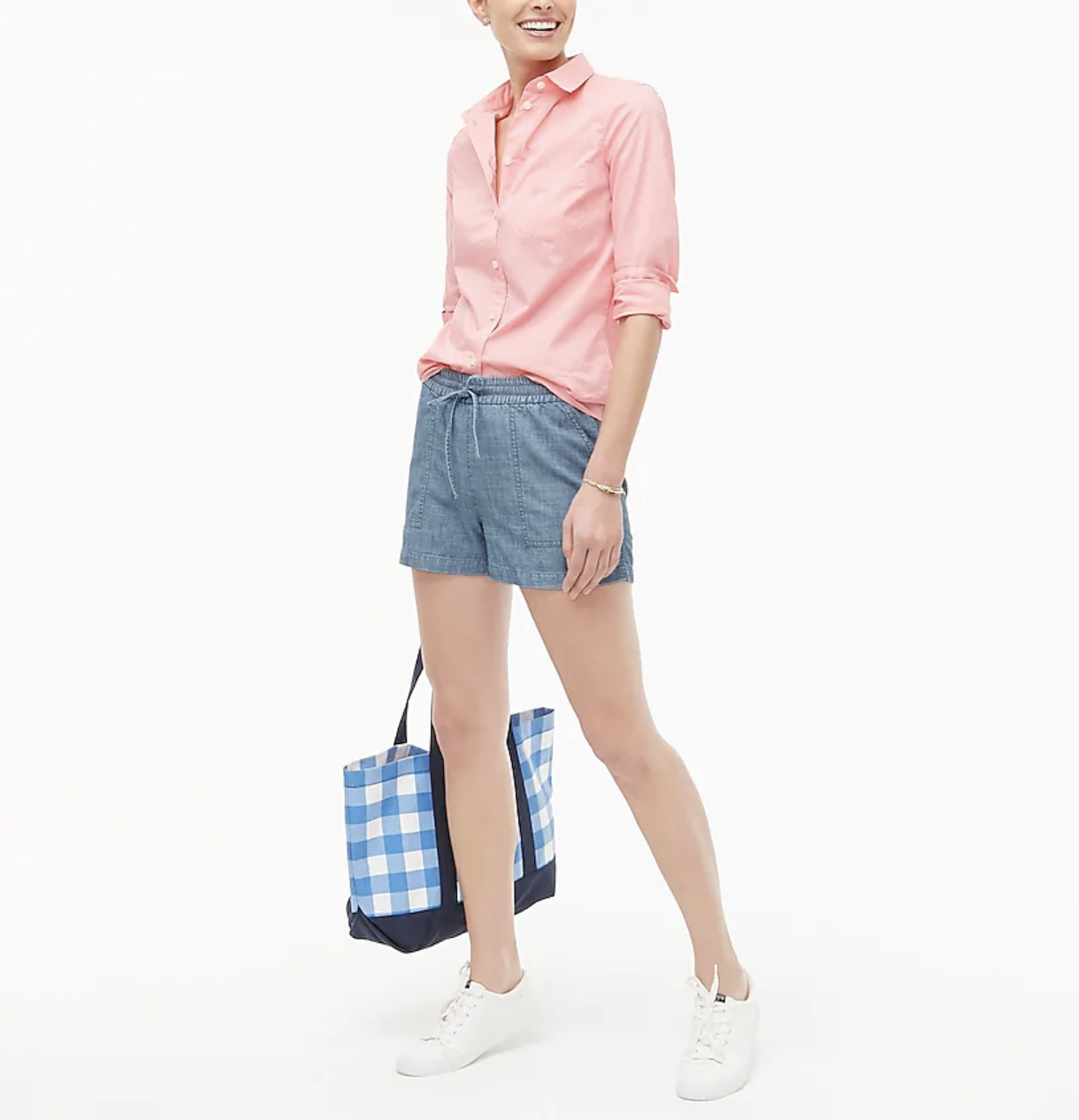 A model wears chambray drawstring short with a pink shirt and white canvas sneakers