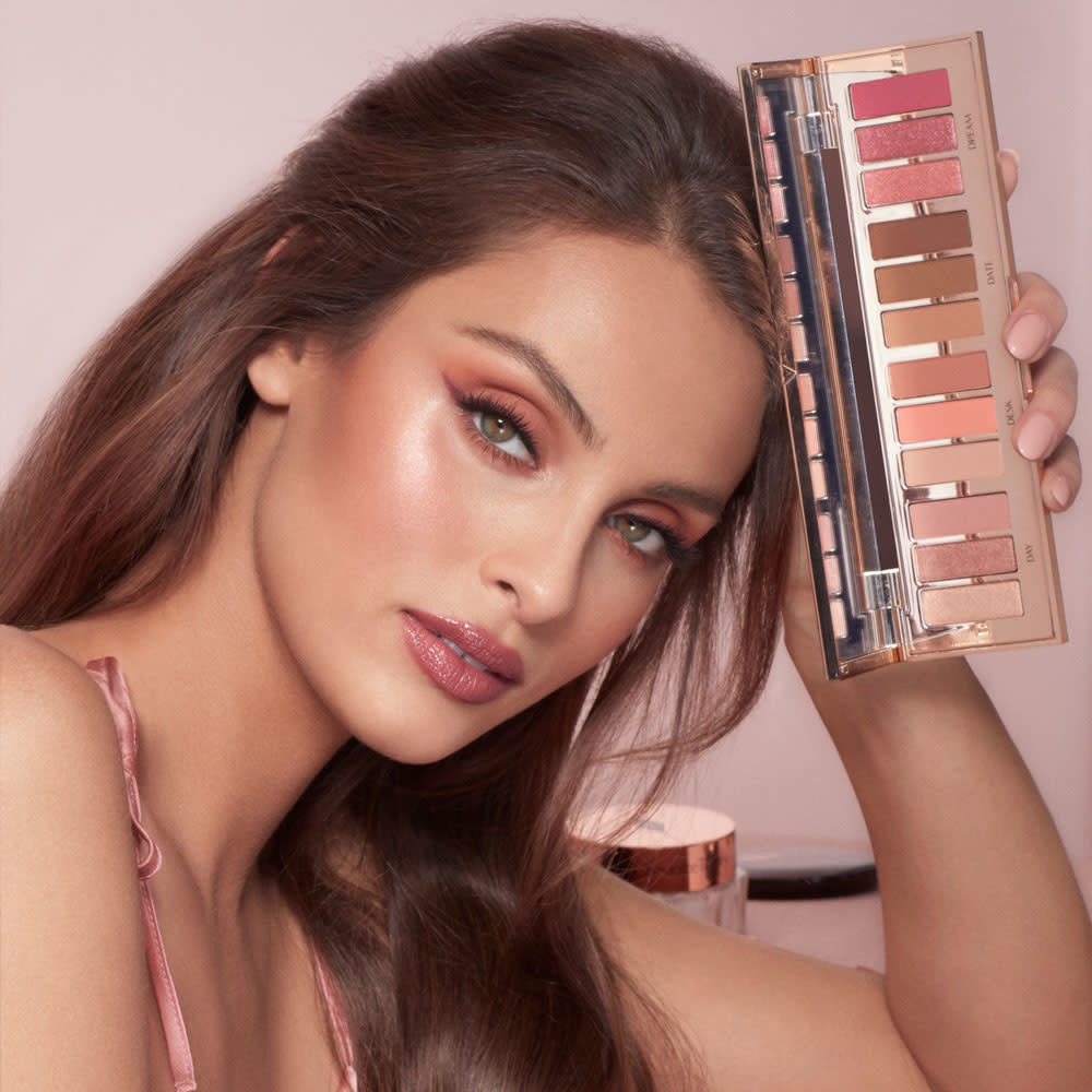 A model holding a 12-shade eyeshadow palette to her head. The palette features nude, pink, and brown tones
