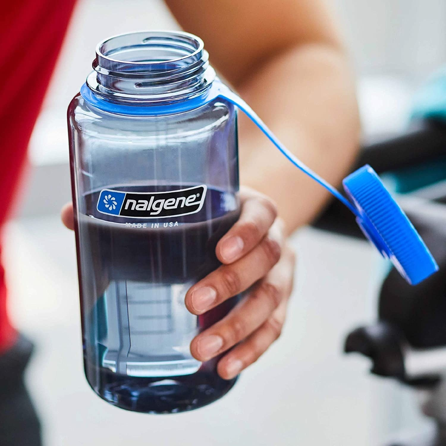A clear Nalgene bottle with a blue top filled with water