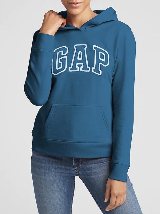 a woman wearing a teal sweatshirt that says GAP