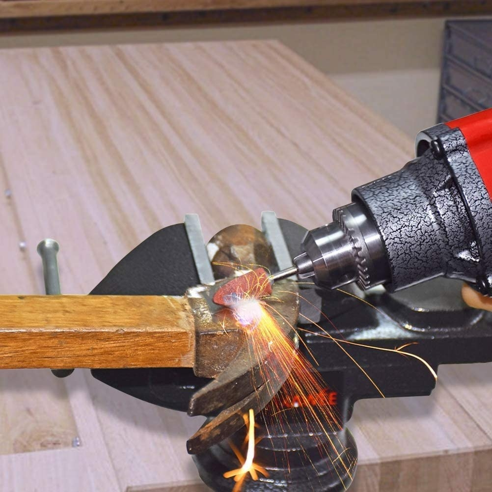 A rotary tool grinding a hammer head in a vice