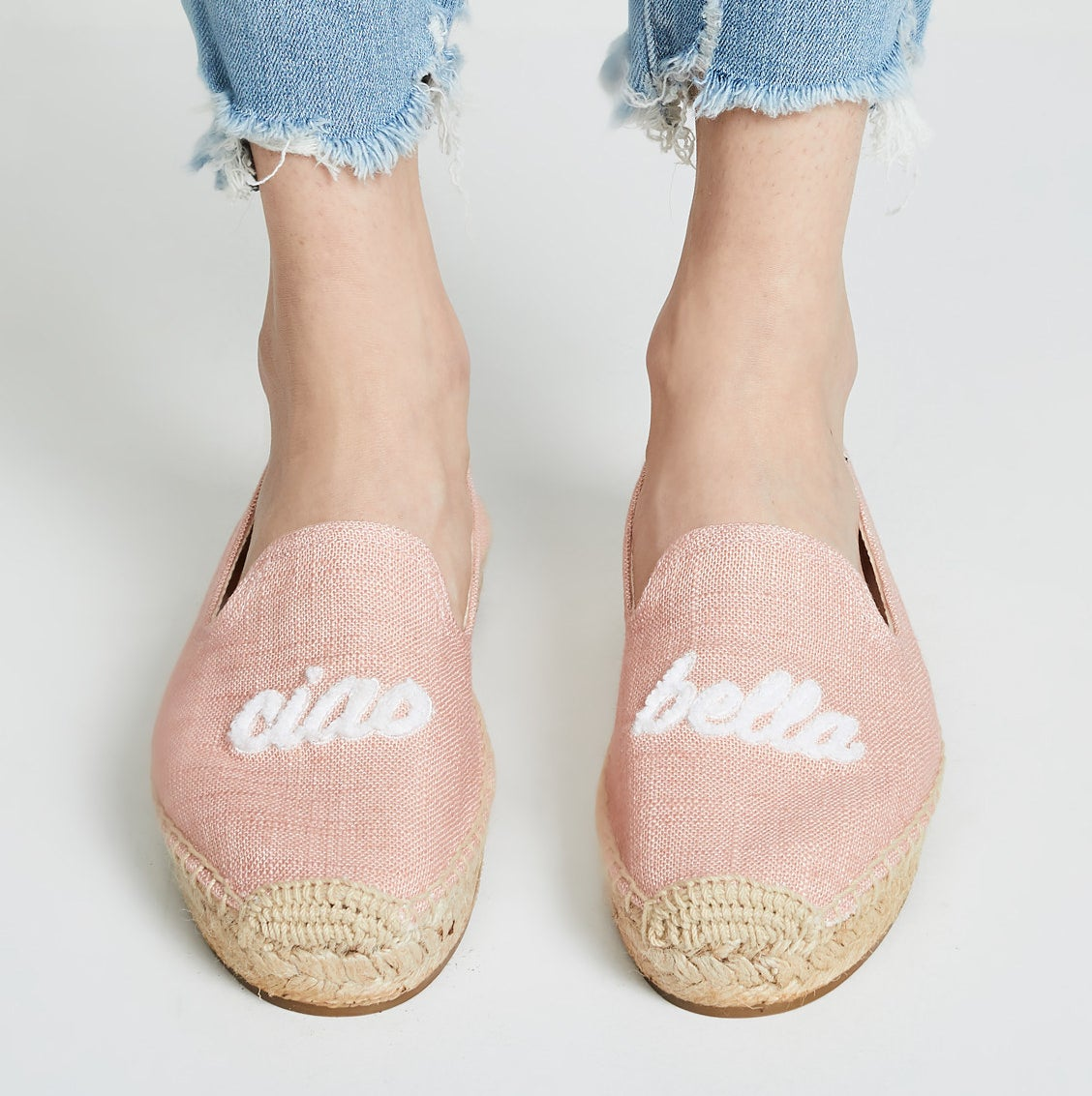 Model wearing pale pink espadrilles with woven bottom and ciao and bella stitched on the front