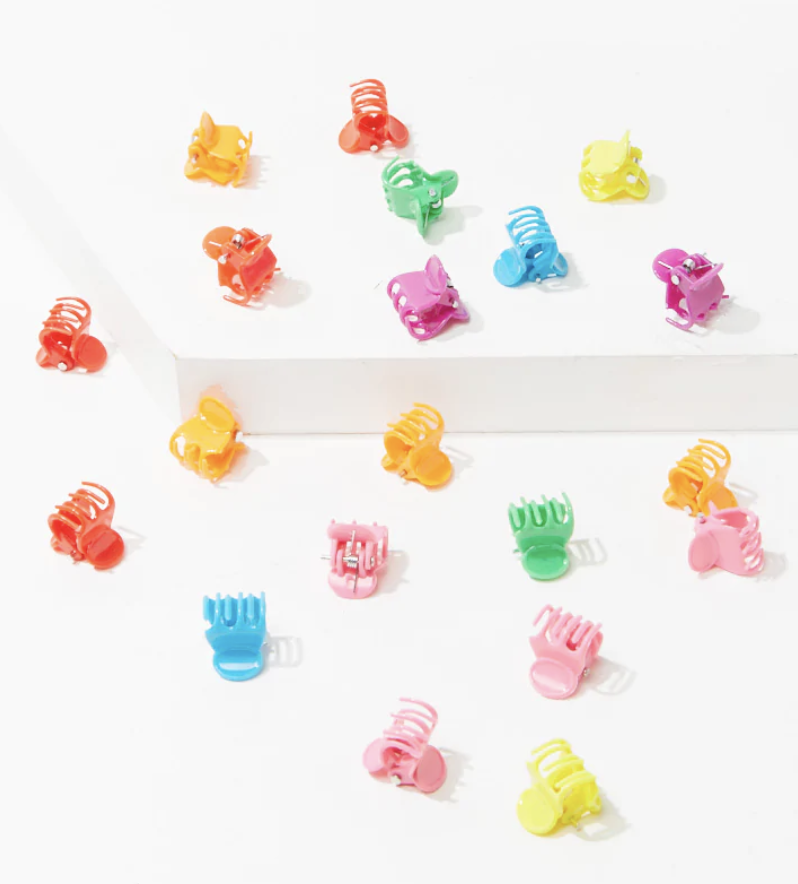 A bunch of brightly-colored tiny hair clips scattered on a surface