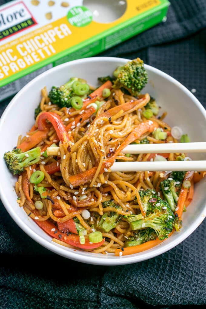 A big bowl of sesame noodles with broccoli, carrots, pepper, and scallions.