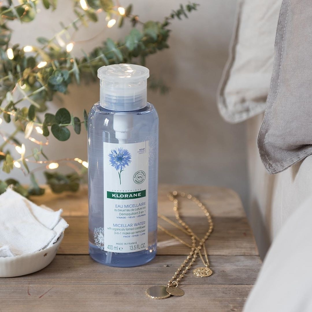 A bottle of the Klorane Micellar Water sitting on a wooden desk next to a bed