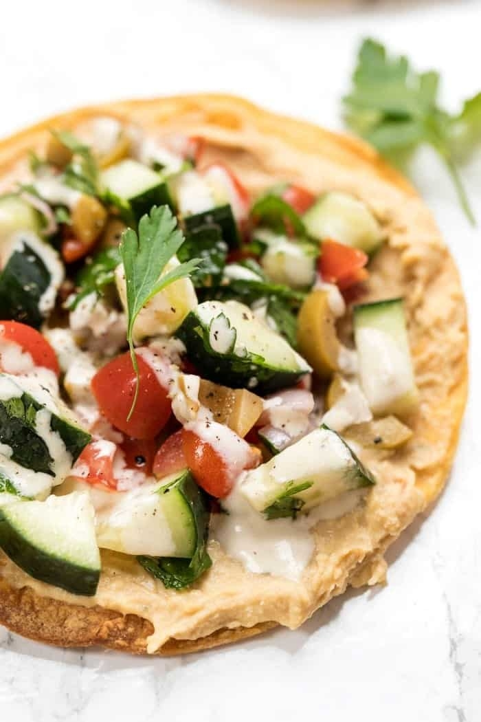 A tostada topped with hummus, chopped tomatoes, cucumbers, and parsley.