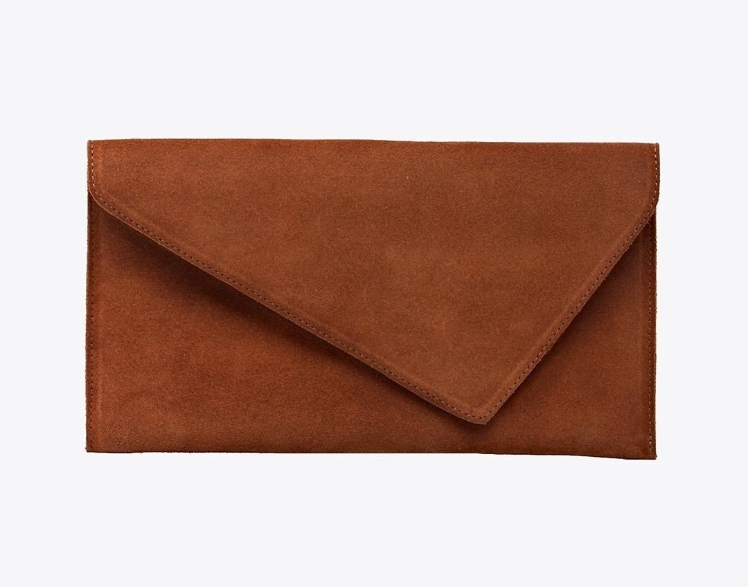 A brown suede clutch with a pointed flap that points to the right