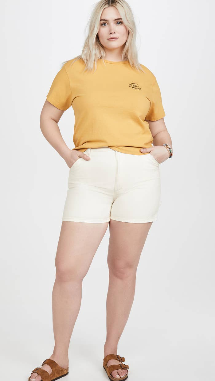 A plus-size model wearing the shorts with tan Birkenstocks and a mustard T-shirt