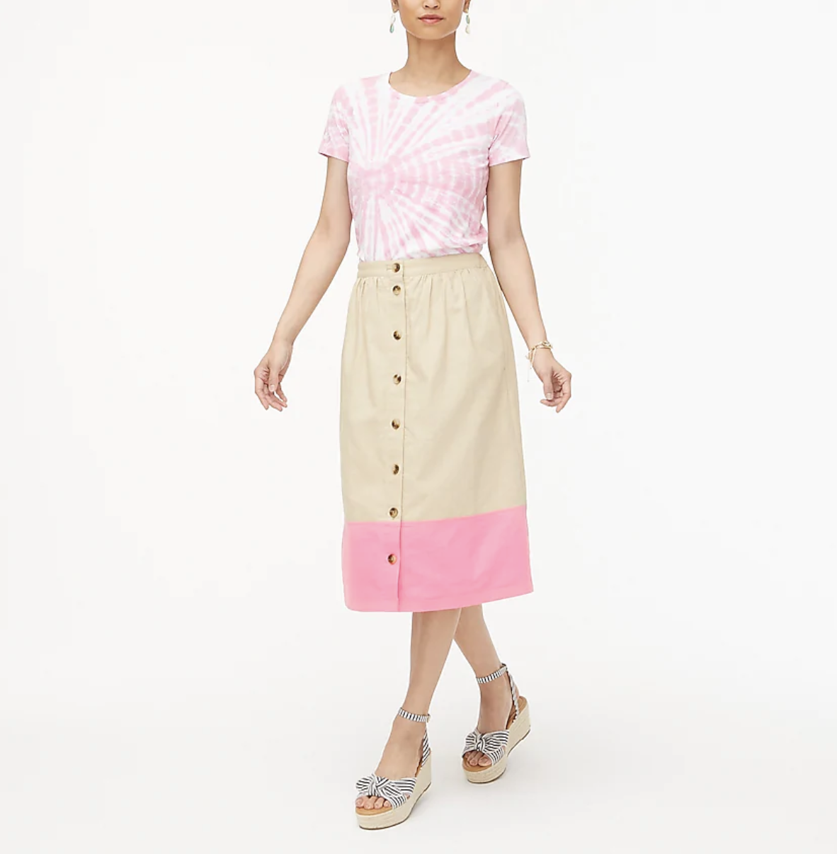 A model wears a white and pink colorblock midi skirt with wedges