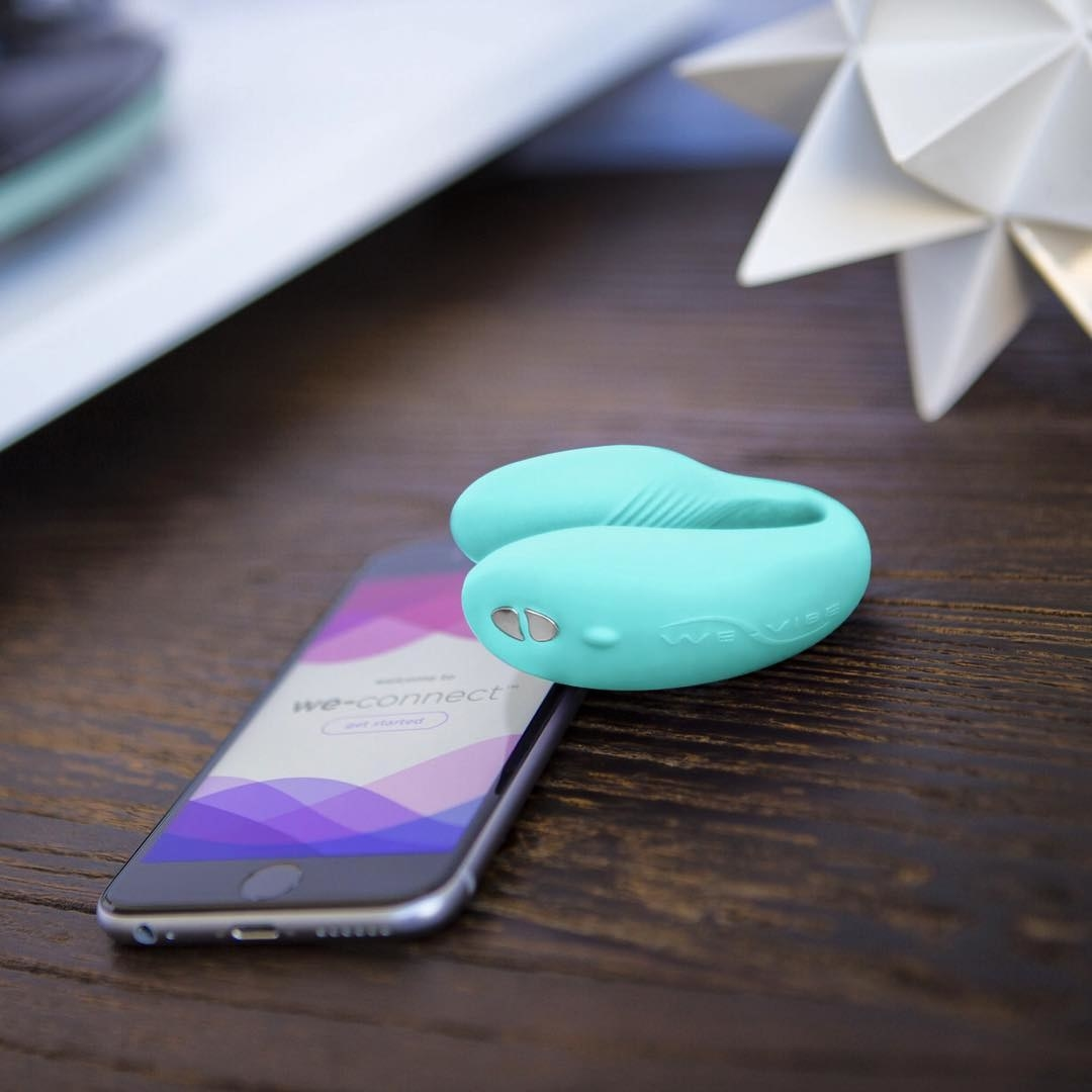The curved U-shaped vibrator with a phone to show the app