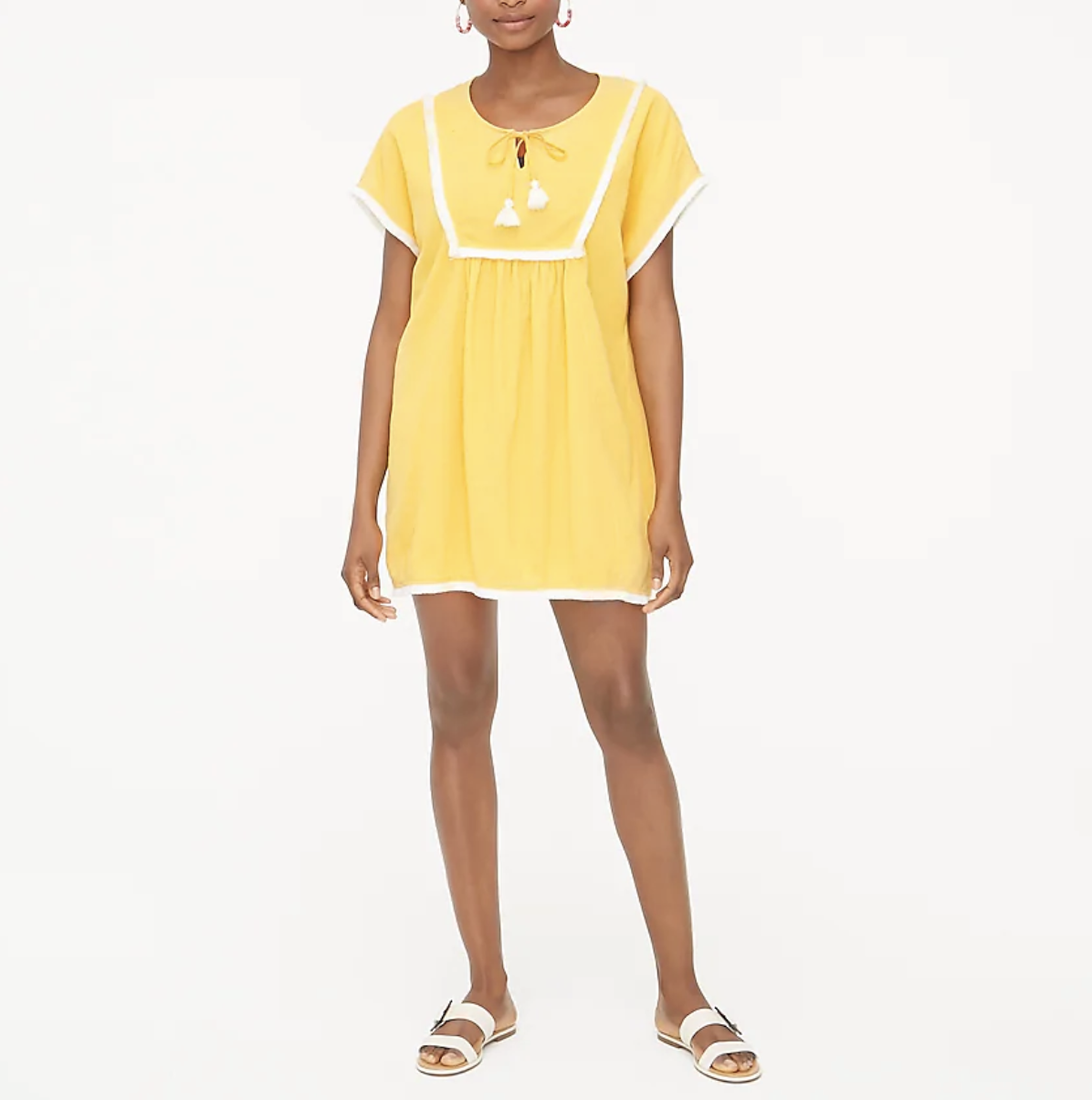 A  model wears a yellow fringe tunic with white sandals