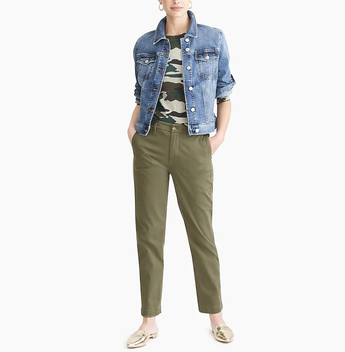 A model wears a classic jean jacket with a camo-print tee, green pants, and gold flats