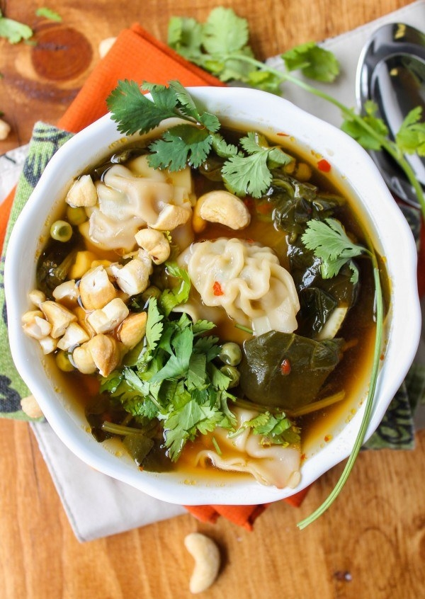 A bowl of wonton soup with fresh herbs.