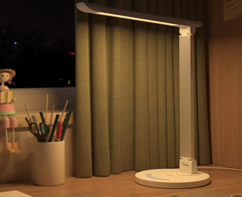 The lamp, which has a circular base and an L-shaped stand and light, propped on a desk