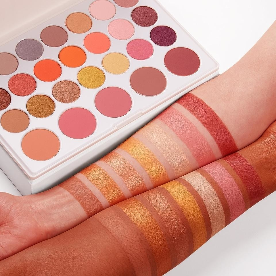 An eyeshadow palette with golden and pink shades swatched across light and deep skin tones