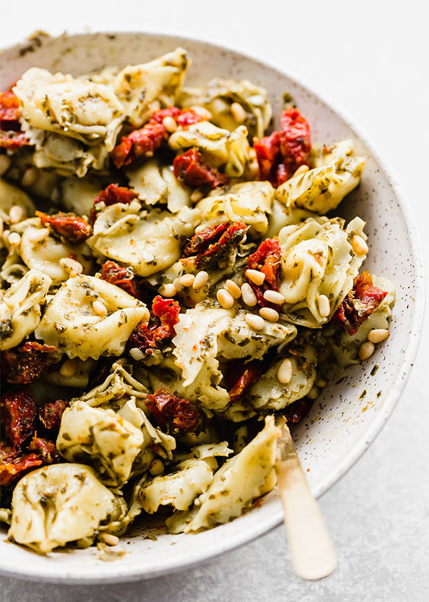 A bowl of tortellini pasta salad tossed with pesto, sun dried tomatoes, and pine nuts.