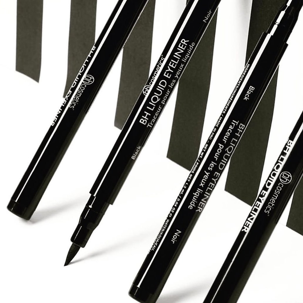 Four liquid eyeliner pens leaning against a surface