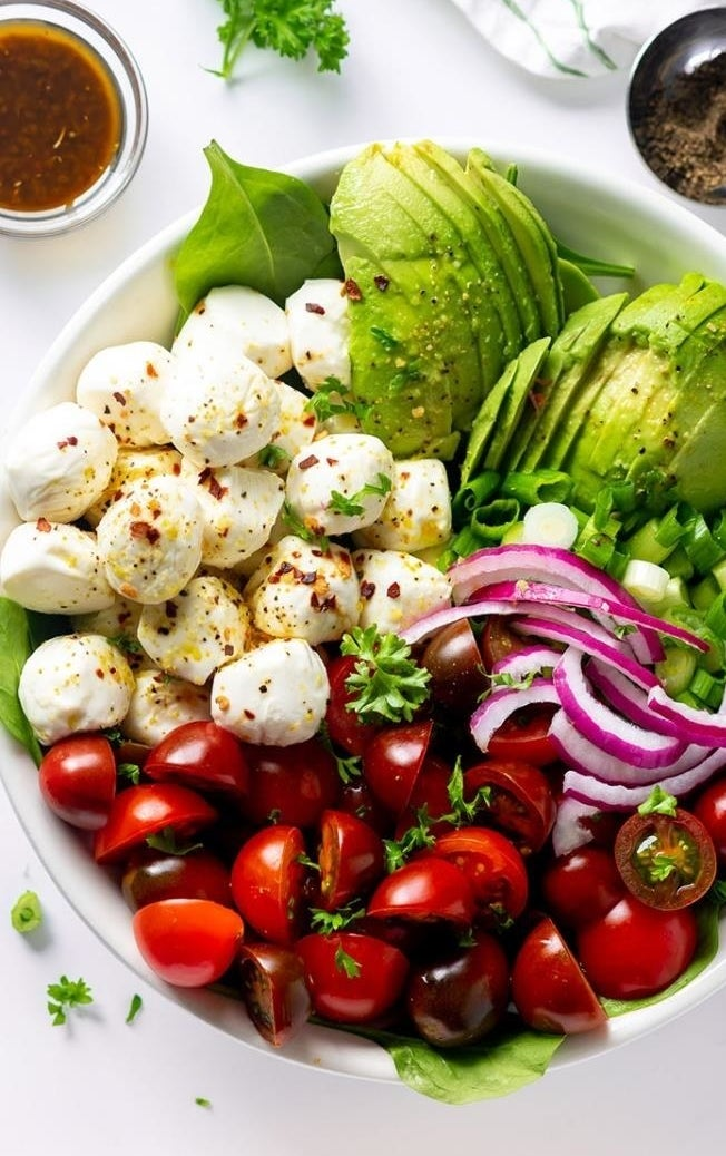 A big salad made with chopped cherry tomatoes, bocconcini, sliced avocado, red pepper, and balsamic dressing on the side.