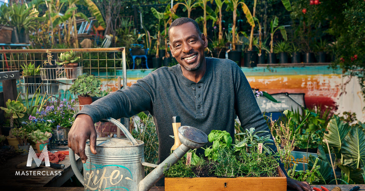 Instructor Ron Finley standing behind a table of planters in a garden