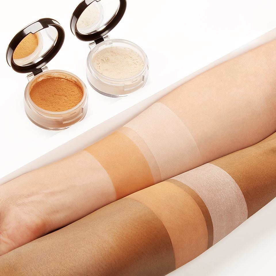 Two powder compacts in a light shade and a tan shade with swatches across light and deep skin tones