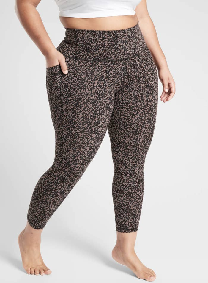 An Athleta model wears the Salutation Stash Pocket II Gravel 7/8 Tight in a mineral brown color