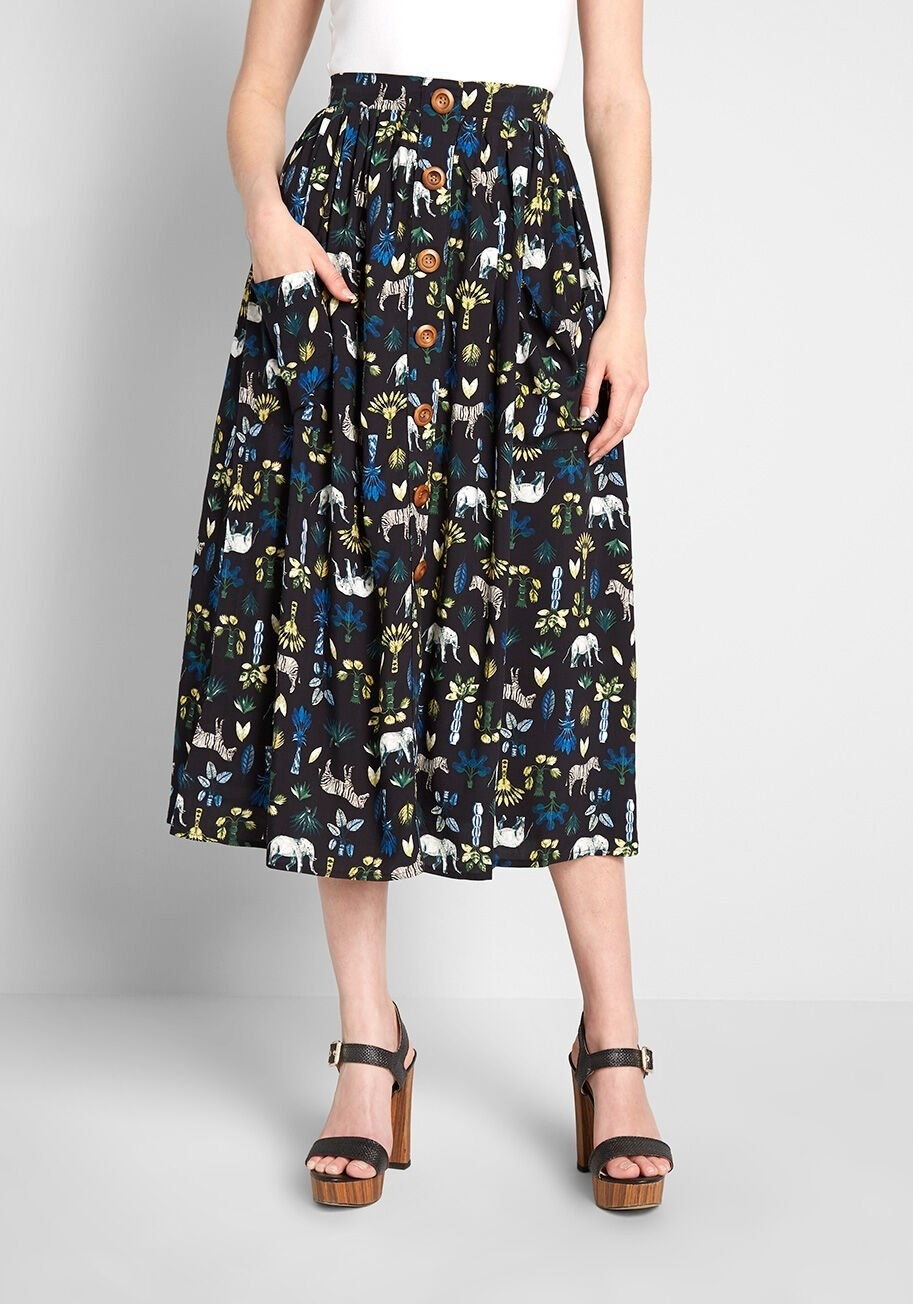 A model wearing the skirt, which is also printed with little plants