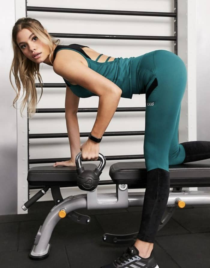 An Asos model wears a teal ASOS 4505 slim fit tank with a cut-out back design