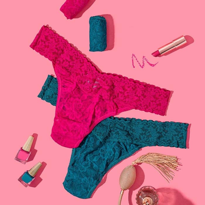 Flatlay of two Signature Lace Original Rise thongs in pink and teal