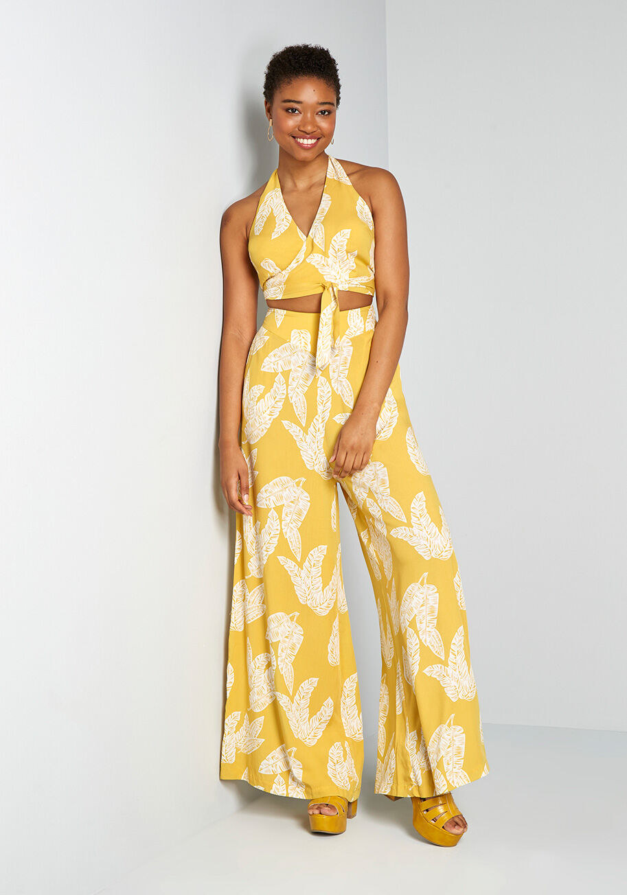 A model wearing the pants, which are yellow and printed with white leaves