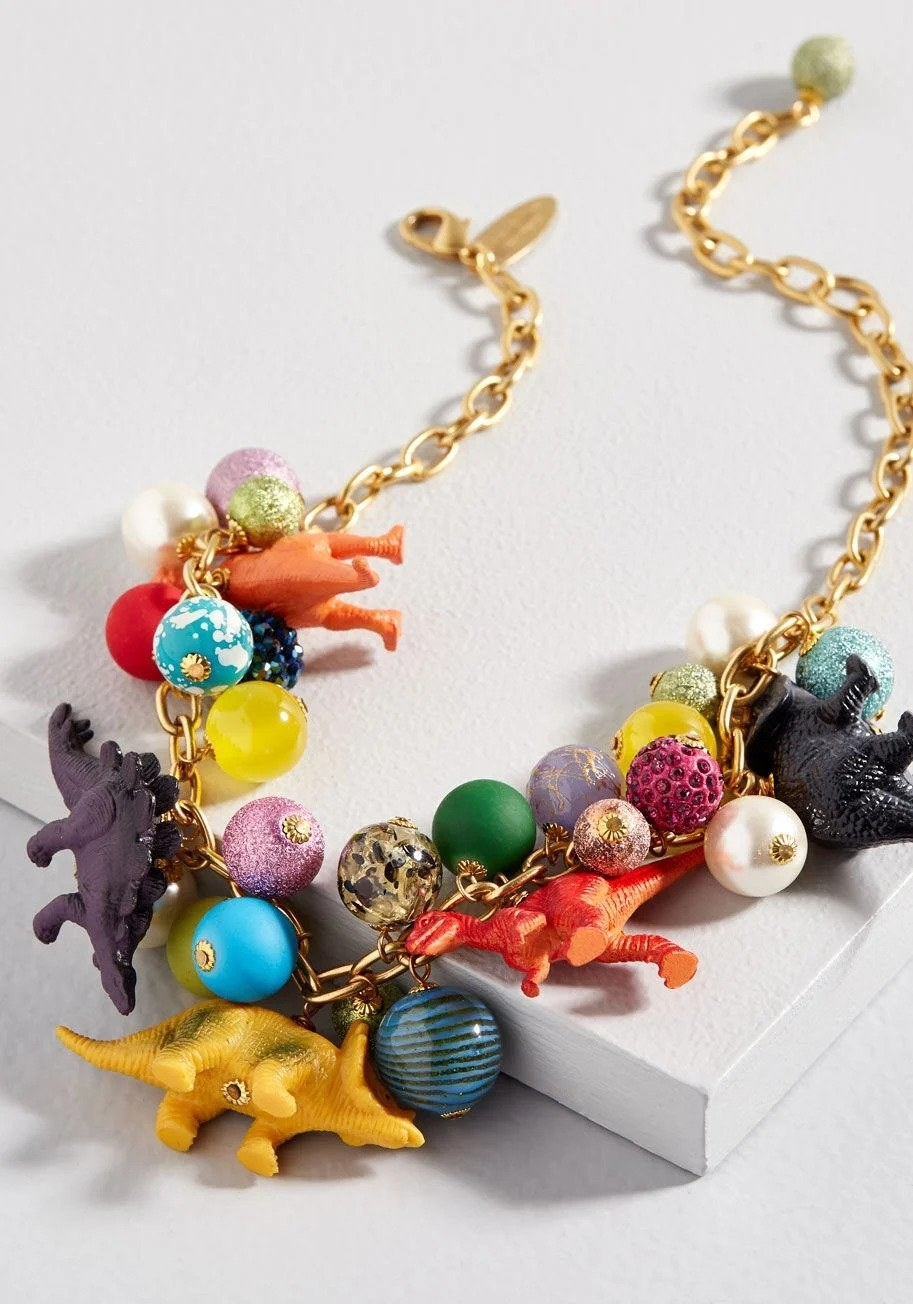 a necklace with dinosaur figures and colorful baubles