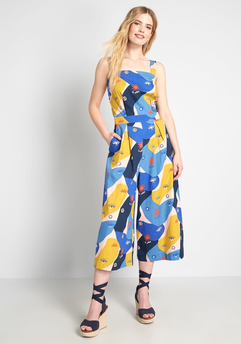 A model wearing the sleeveless jumpsuit in a colorful print that kind of looks like abstract faces, with little eyes printed on it