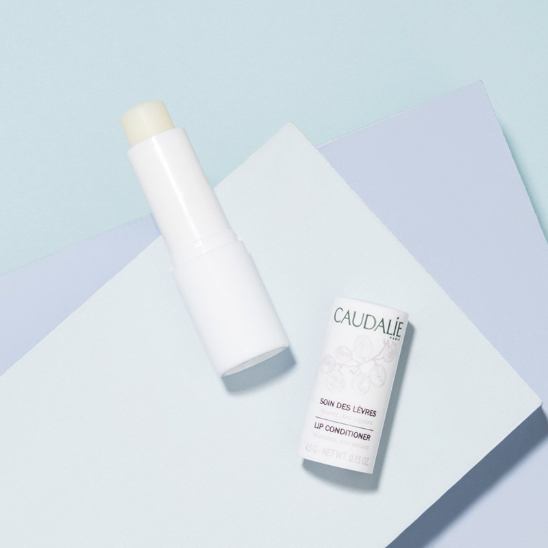 A flat lay photo of an uncapped tube of light-colored lip balm