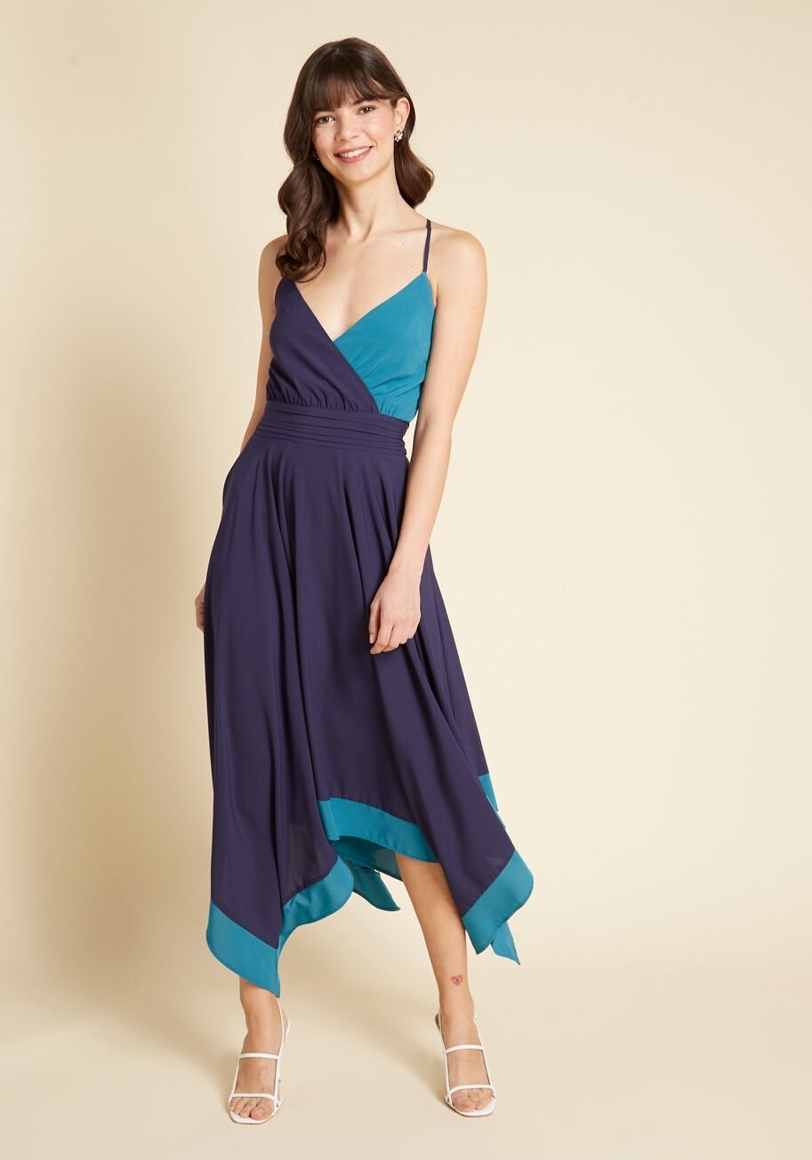 A model wearing the dress, which is colorblocked with navy and teal and has a deep V-neckline
