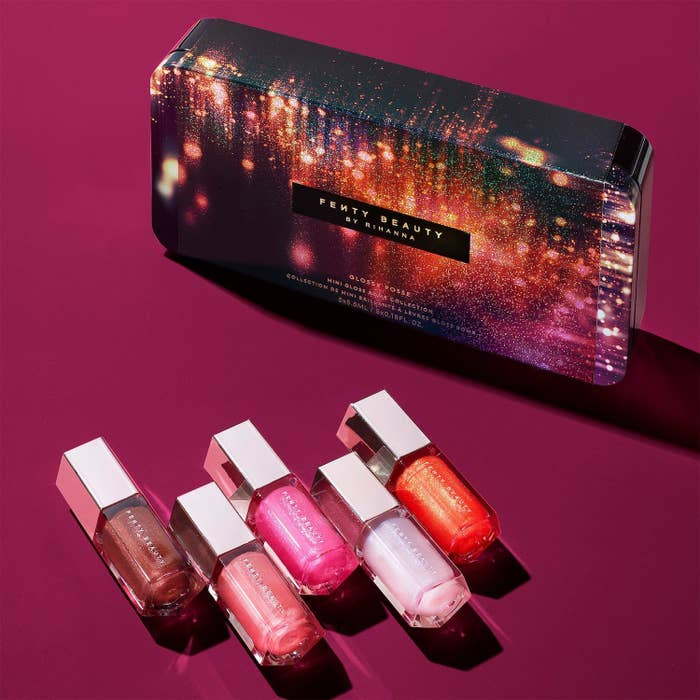 sparkly-looking packaging for the glosses next to the five glosses which are all shimmery and include shades of bergundy, three pinks, and orange