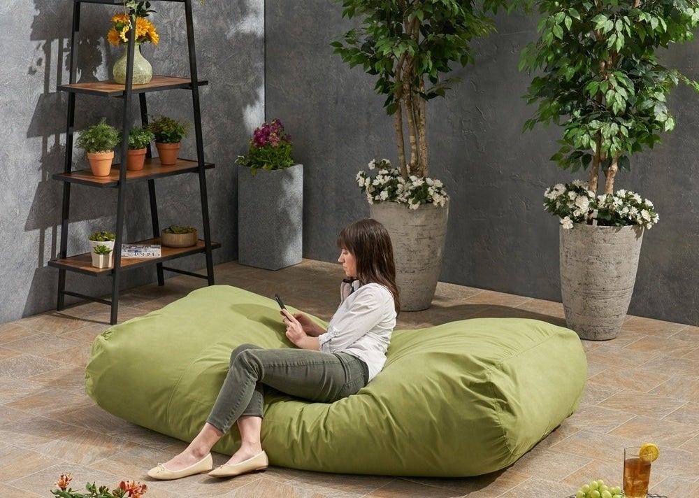 A person on the green lounger bean bag