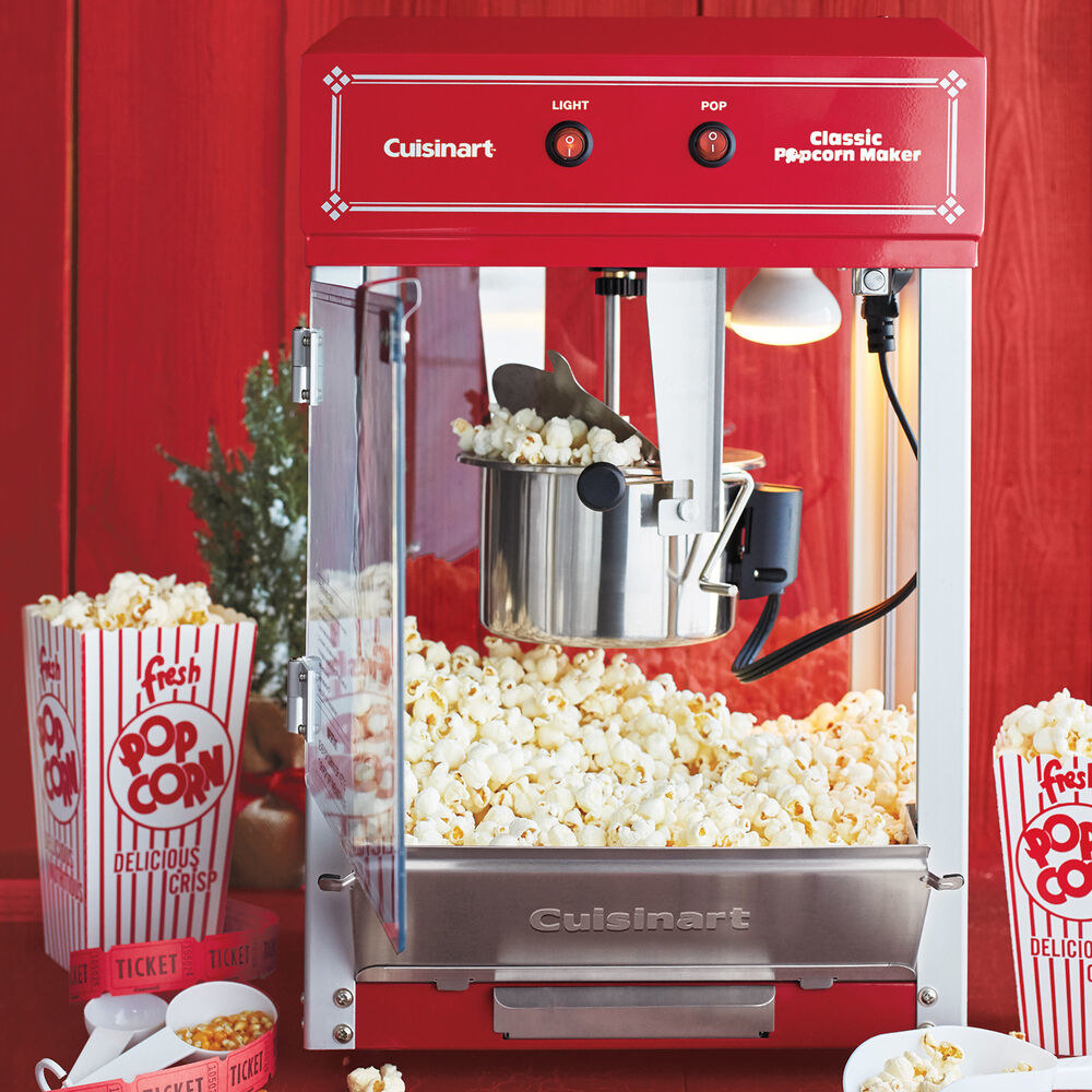 mini version of movie theatre popcorn maker, a cube with a silver pot hanging from the top where the popcorn spills out into the bottom to be scooped