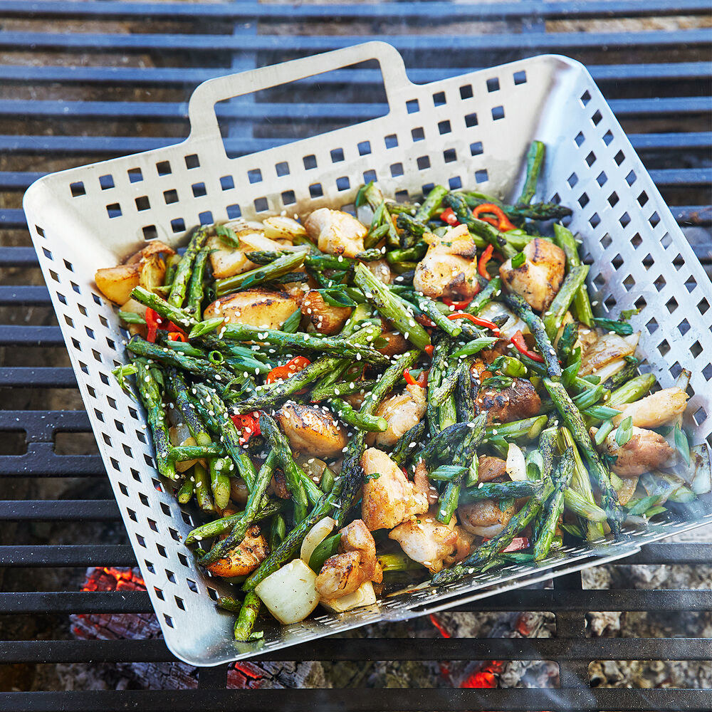 square metal basket with metal handles full of veggies on a grill