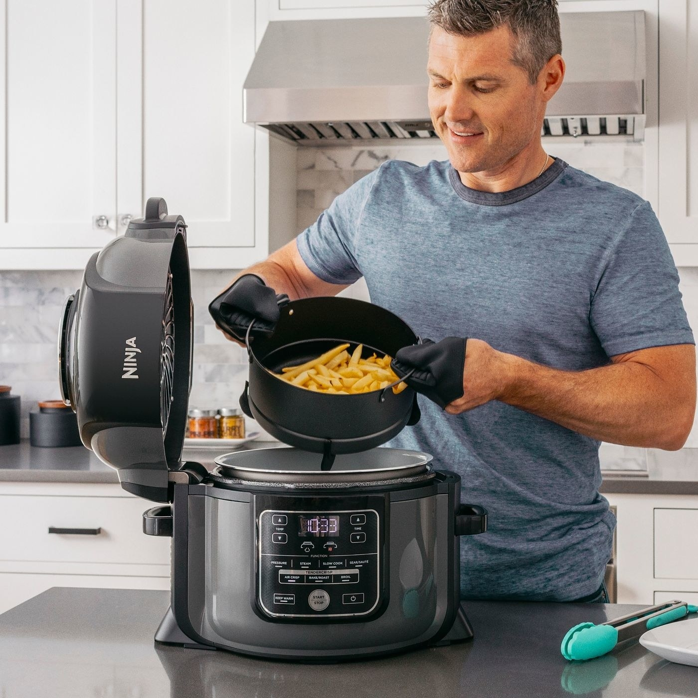Person removing cooked French fries from the air fryer