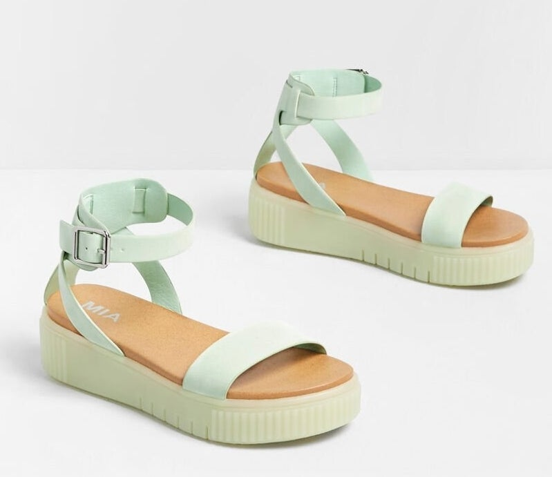 The sandals, which have a buckled ankle strap and rubbery, thick soles