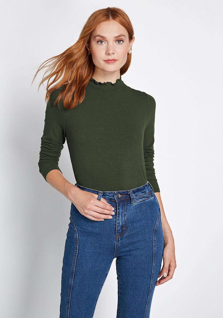 a model wears an olive top