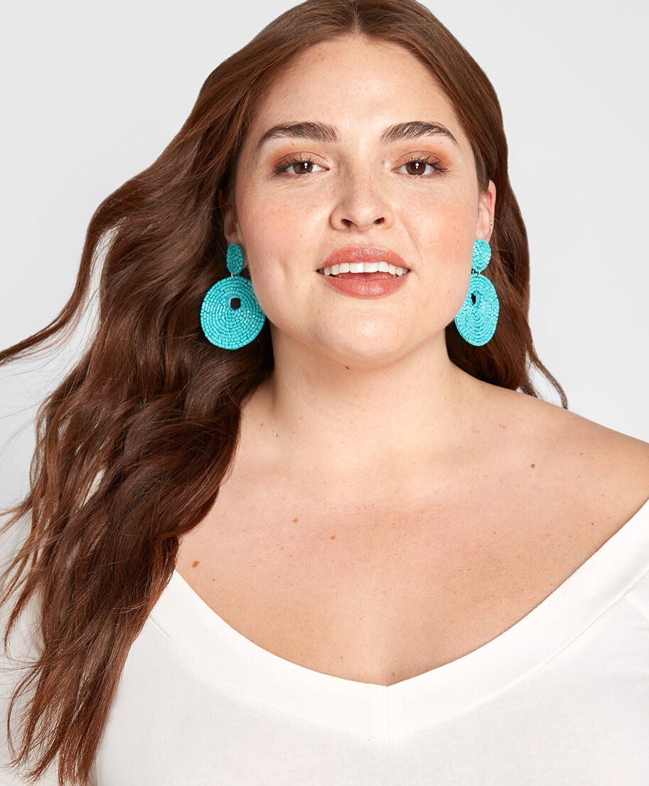 A model wearing the turquoise-colored earrings, which drop to be just about level with  the bottom of their jaw