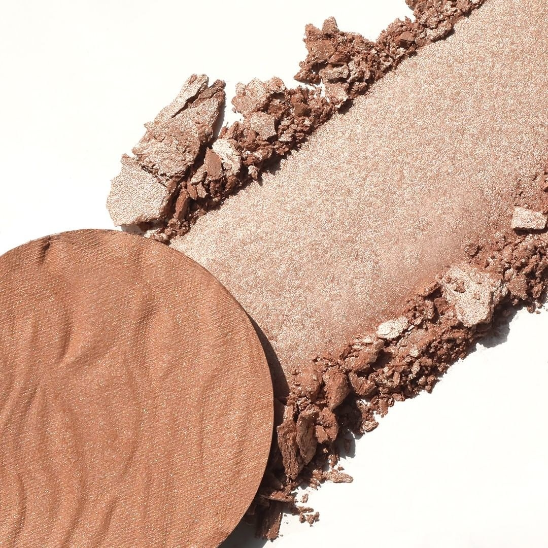 a circle of the bronzer removed from the packaging to show how the formula is creamy, shimmery, and powdery