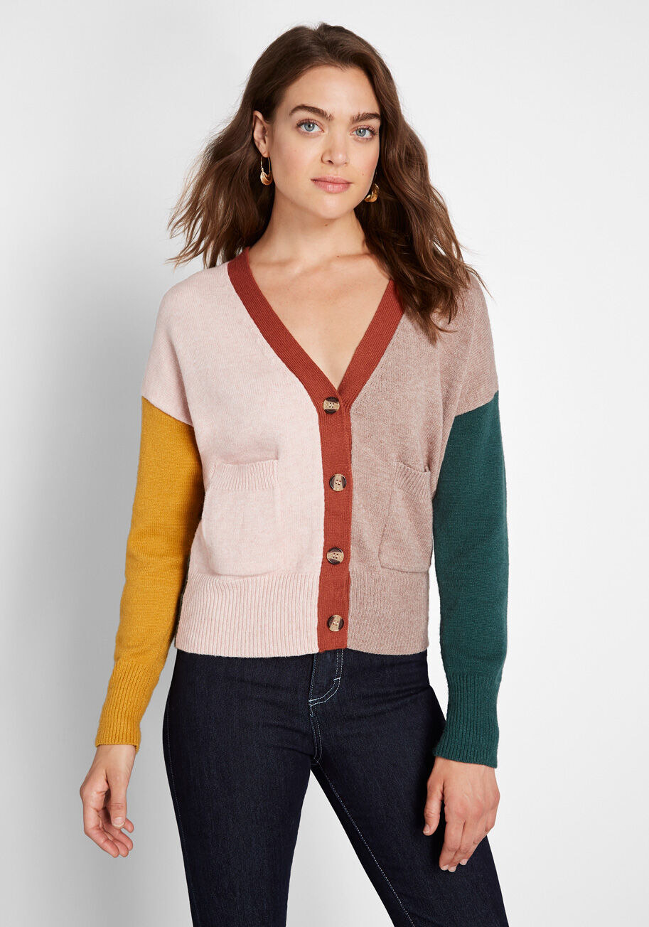a pink cardigan with a yellow sleeve, green sleeve, and red middle