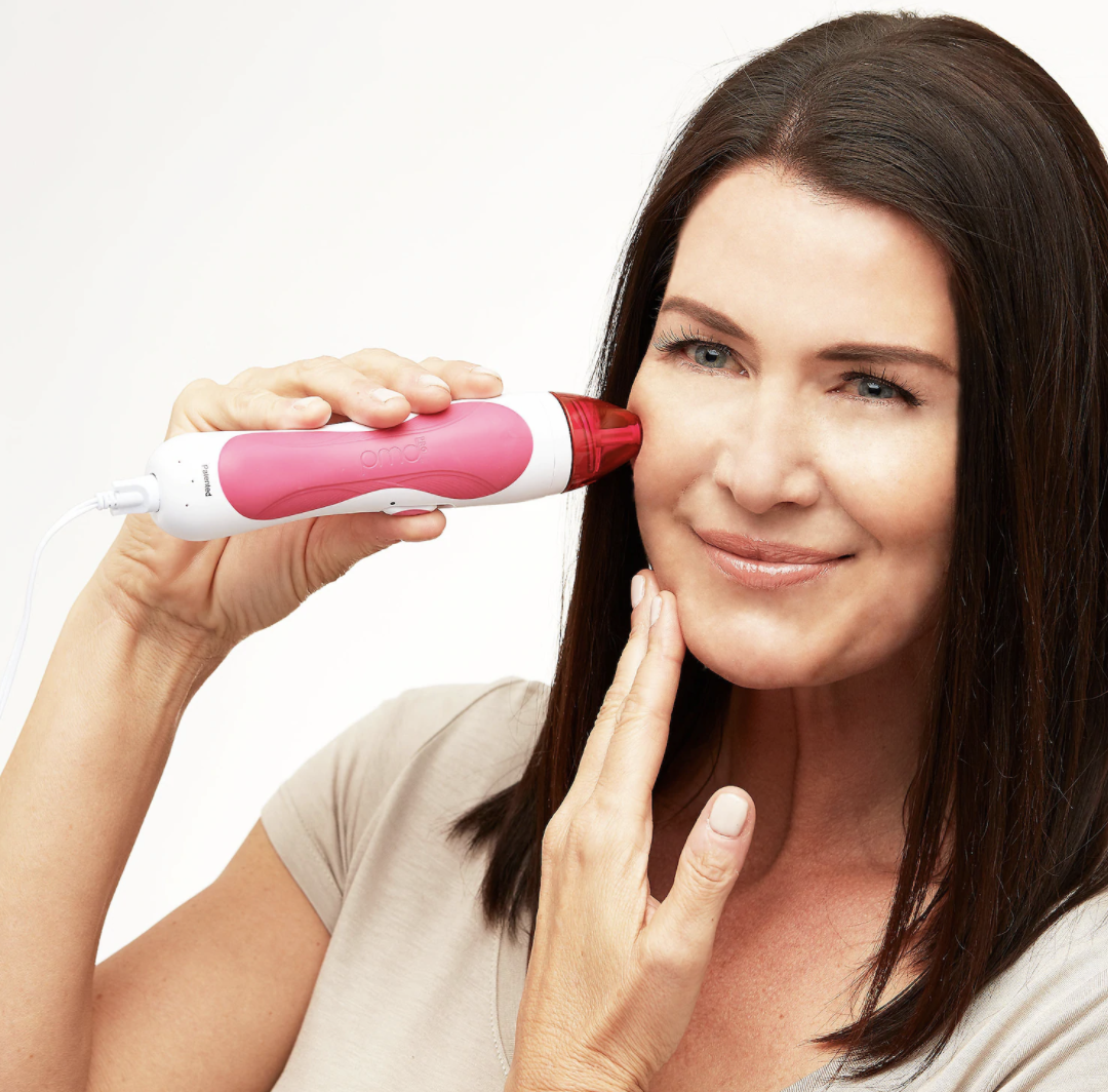 someone holding the personal microderm pro (which looks long and tubular in shape) up against their cheek