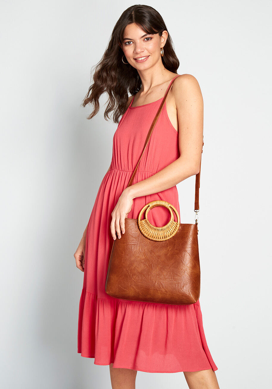 A model carrying the bag with the strap on their shoulder. It comes to her hip and the bag itself is about the size of two loaves of bread